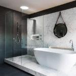 Salle de bain noir et blanc avec podium en marbre et panneau mural