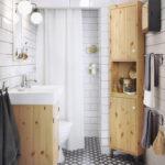 Salle de bain blanche avec murs carrelés et motif géométrique au sol