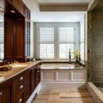 Salle de bain dans une armoire de maison privée avec lavabo, baignoire et douche