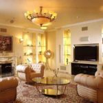 Phòng khách với ghế bành bọc da và bàn cà phê bằng kính