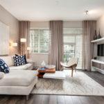 Trang trí phòng khách màu be nhạt với ghế sofa và rèm ngang trên cửa sổ.