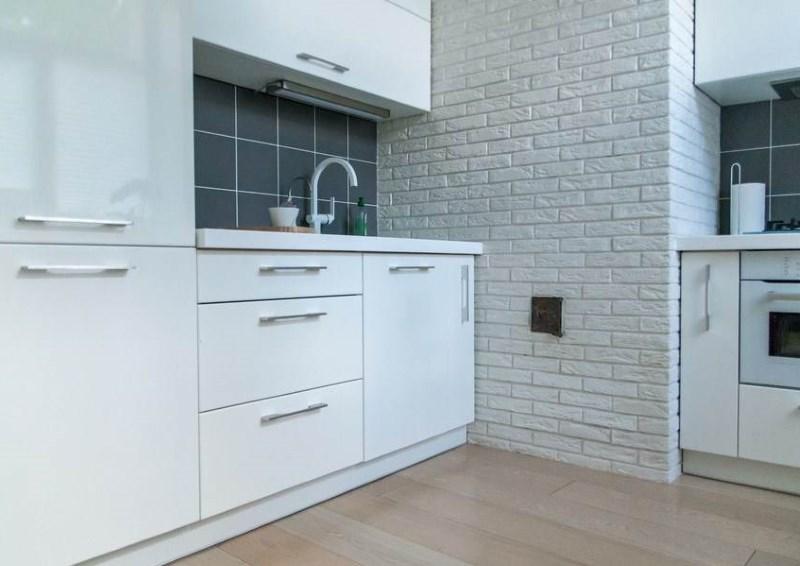 Interior de bucătărie alb minimalist cu perete de cărămidă