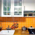 Șorț cu gresie portocalie într-o bucătărie cu panou