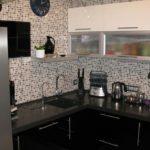 Bucătărie neagră în bucătărie într-o casă cu panouri