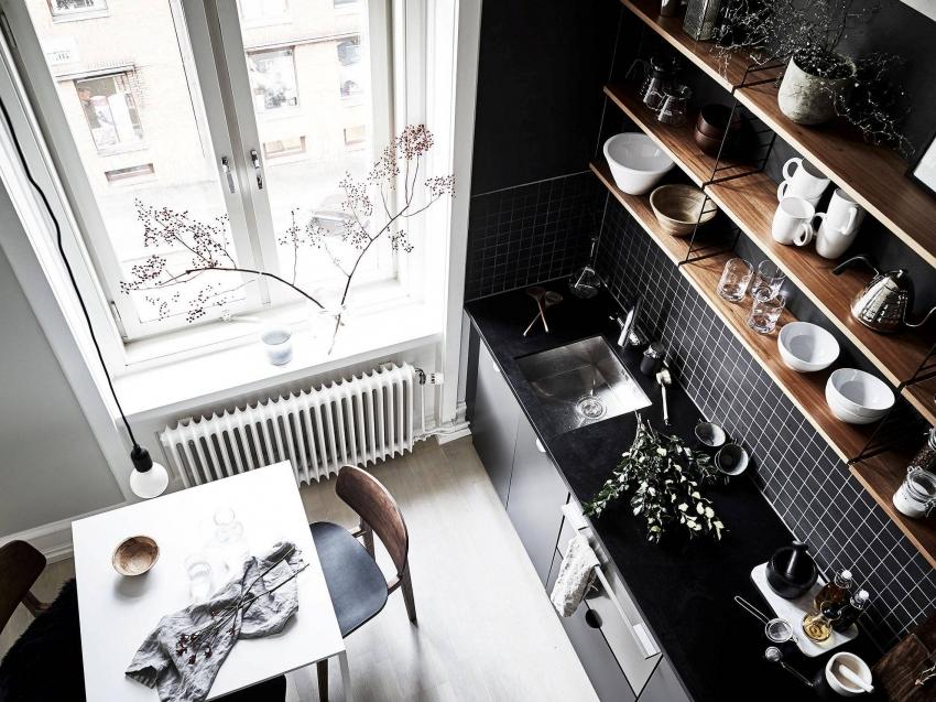 Interiorul bucătăriei în alb și negru cu rafturi din lemn.