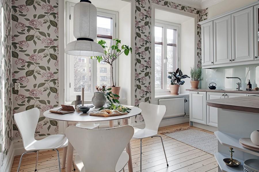 Feuilles vertes sur le papier peint dans la cuisine avec des meubles blancs