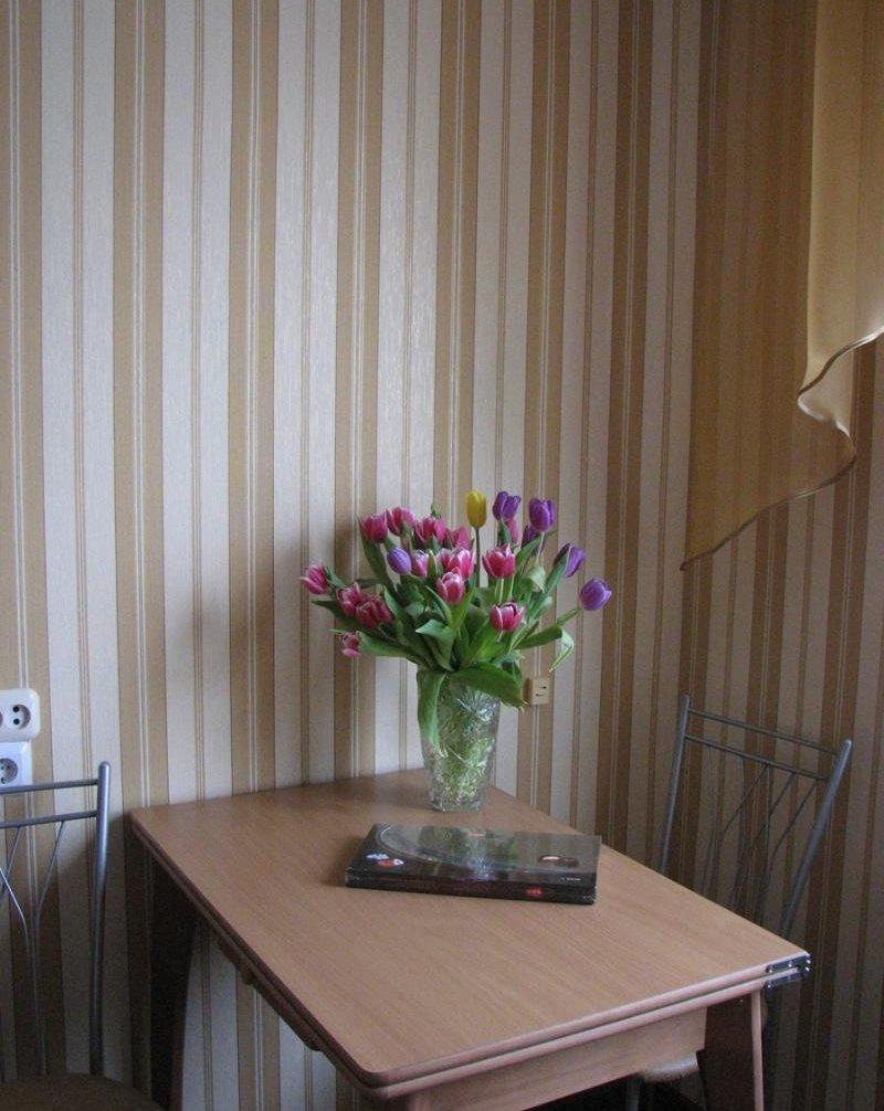 Masă de luat masa lângă perete cu tapet cu dungi