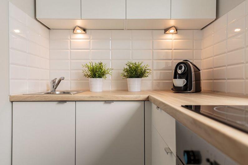 Lămpi mici sub dulapurile suspendate într-o bucătărie compactă