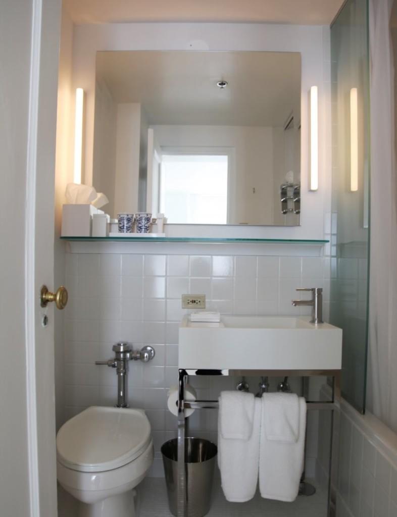 Petite toilette avec un grand miroir sur le mur