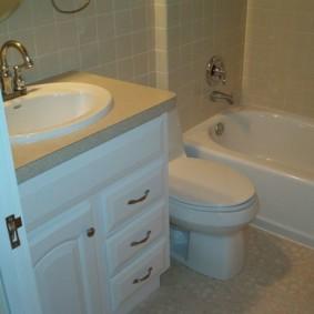 Armoire avec lavabo près de la porte dans la salle de bain