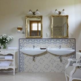 Hai tấm gương trong khung mạ vàng trong phòng tắm kết hợp