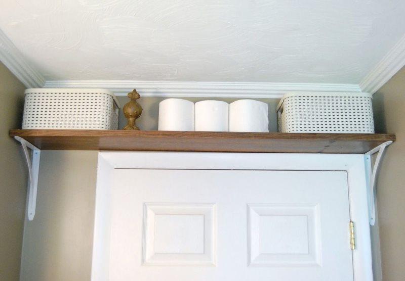 Étagère en bois au-dessus de la porte de la salle de bain