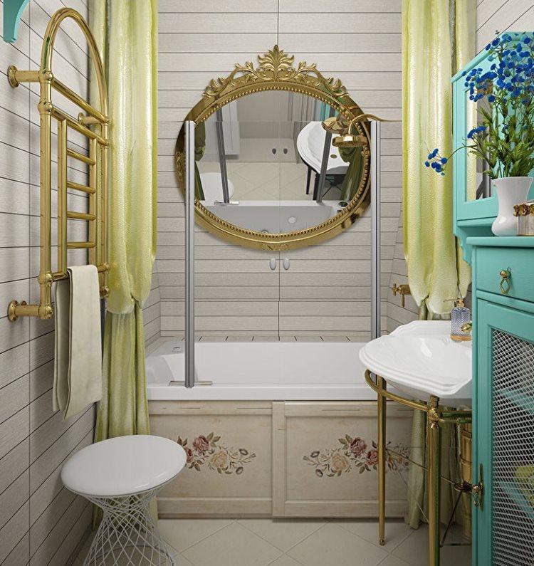مرآة في إطار مذهب على حوض استحمام أبيض