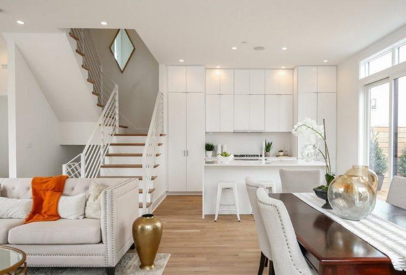 غرفة معيشة ومطبخ مع سلالم إلى الطابق الثاني من منزل خاص