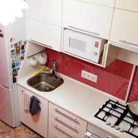 Un évier près du réfrigérateur dans une petite cuisine