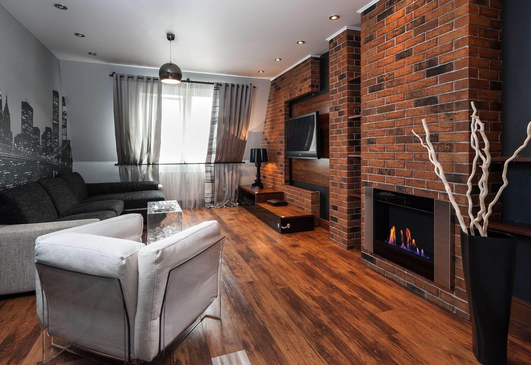 mur de briques avec cheminée et TV dans le salon