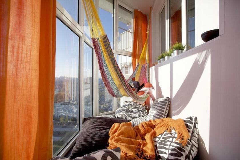 De nombreux oreillers au sol du balcon avec des fenêtres panoramiques