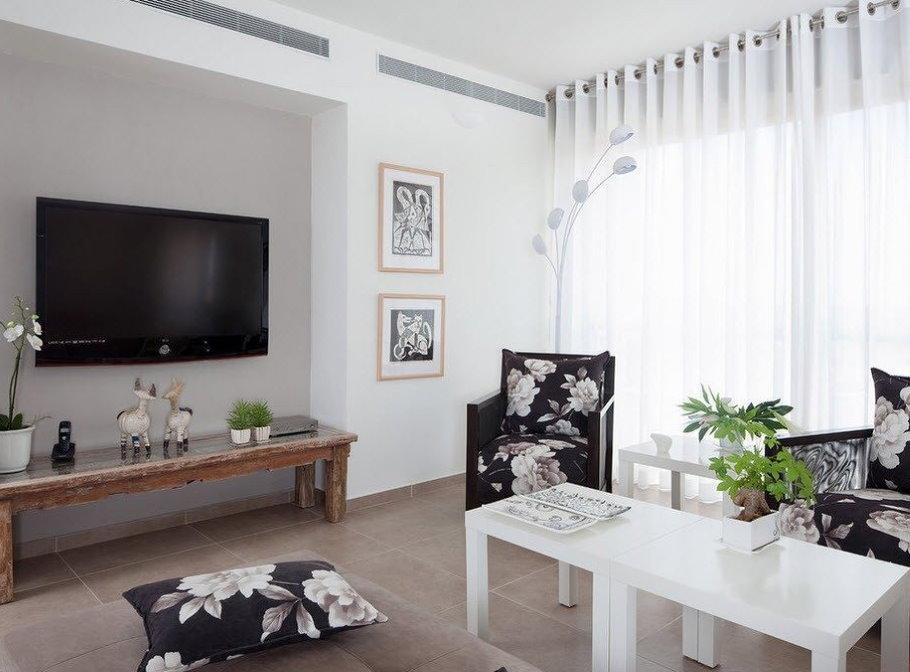 Rideaux blancs sur les œillets dans le salon d'un appartement de deux pièces