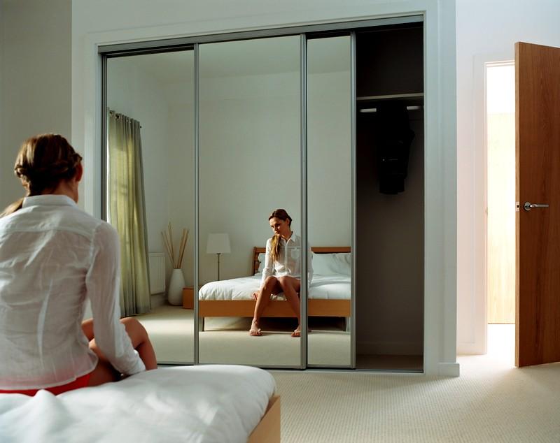Reflet d'une jeune fille dans une armoire à miroir dans une chambre