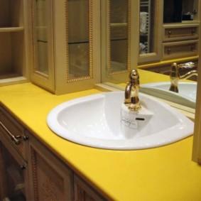 Bồn rửa trắng ở mặt bàn màu vàng