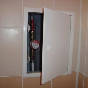 Compteur d'eau derrière la porte entrouverte de la trappe de plomberie