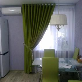 Rideau vert sur la fenêtre de la cuisine dans une maison préfabriquée