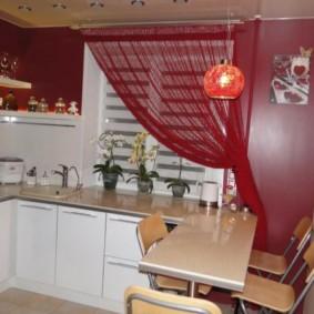 Rideau rouge sur la fenêtre de la cuisine avec des meubles blancs