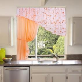 Un évier dans le comptoir devant la fenêtre de la cuisine