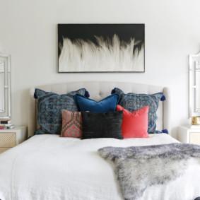 Oreillers multicolores sur un lit haut