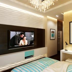 L'intérieur d'une petite chambre avec une télévision sur le mur