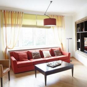 Canapé rouge devant la fenêtre du salon