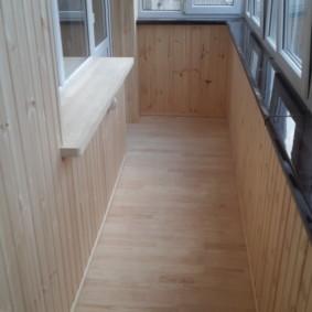 Plancher en bois sur le balcon avec fenêtres en plastique