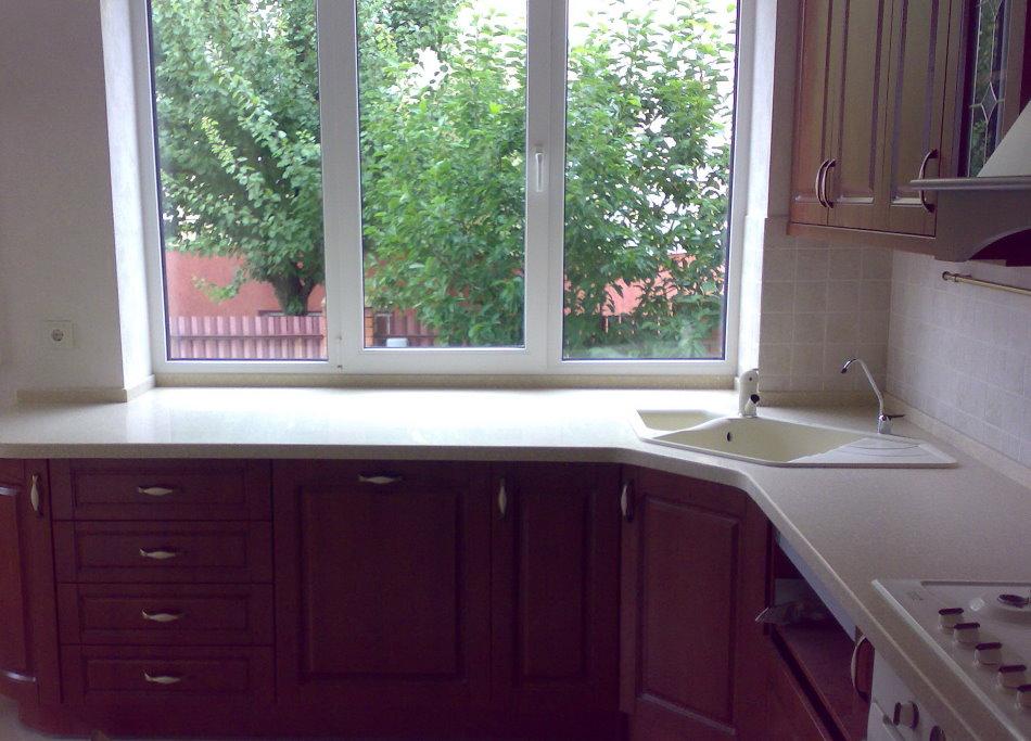 Évier trapézoïdal devant une fenêtre de cuisine dans une maison privée