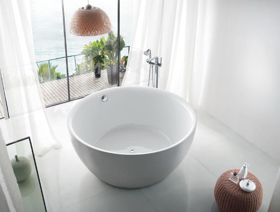 Baignoire ronde en fonte devant une fenêtre panoramique