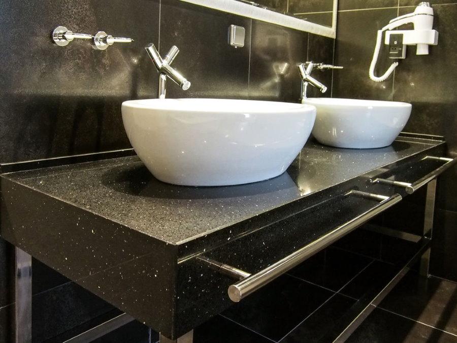 Tay vịn bằng thép không gỉ trên mặt bàn bằng đá trong phòng tắm