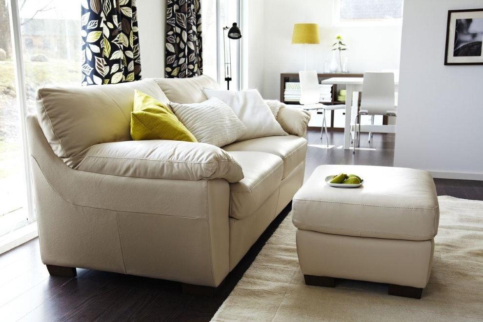 Pouf avec revêtement en cuir devant un canapé dans le salon