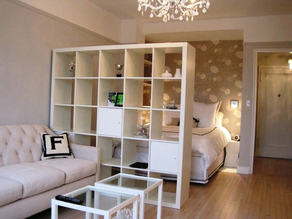 Étagères blanches dans le salon avec un lit