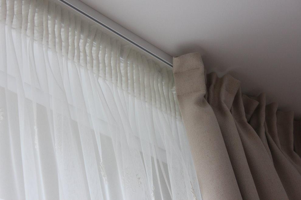 Fixation de tulle sur une corniche en aluminium sous le plafond du salon