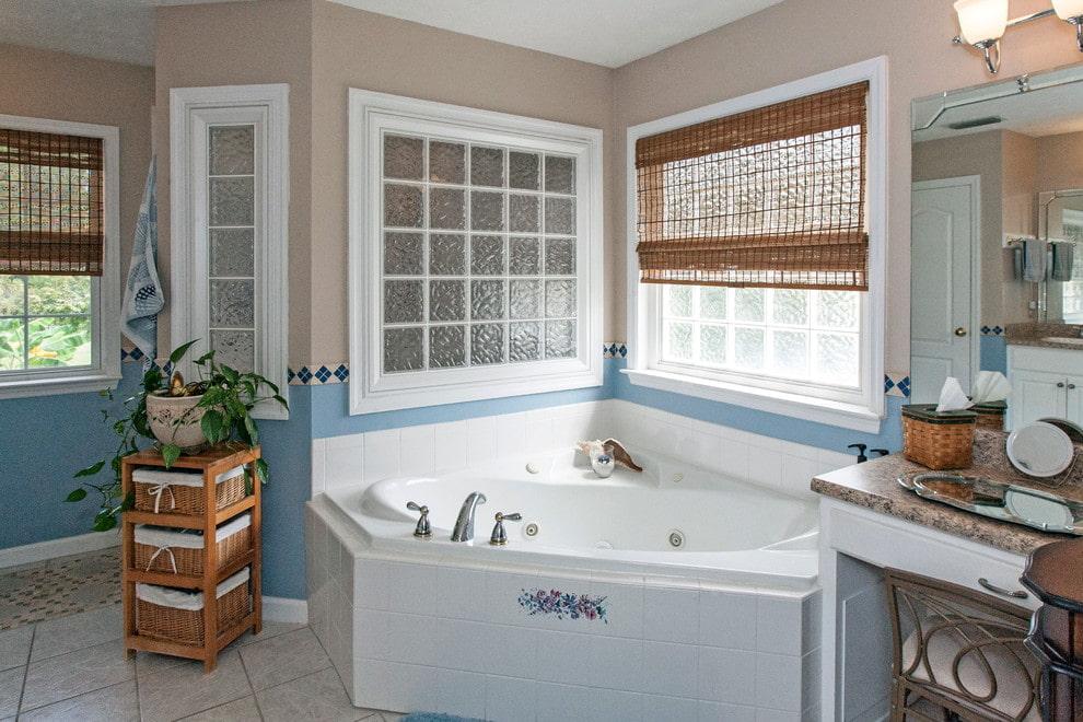 Baignoire d'angle en fonte devant une fenêtre avec un rideau en bambou