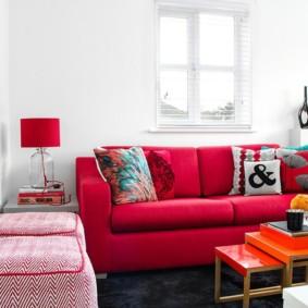 Meubles rouges dans un salon blanc