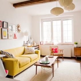 Canapé jaune dans une pièce avec poutres en bois