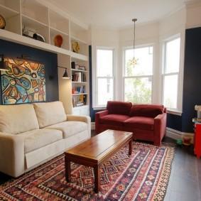 Một chiếc ghế sofa nhỏ trong phòng khách với một cửa sổ bay