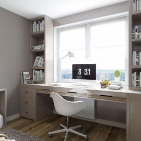 Écran d'ordinateur sur la table devant la fenêtre