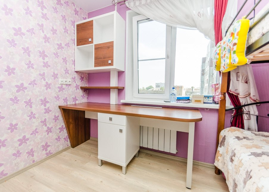 Un bureau sous le rebord de la fenêtre dans la chambre de la fille