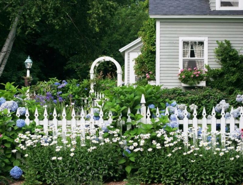 Clôture blanche dans le jardin devant le jardin