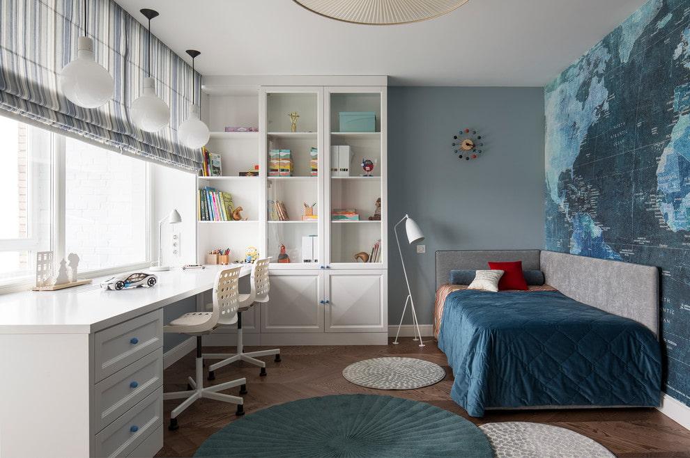 Table blanche avec une armoire devant une fenêtre dans une chambre de garçon