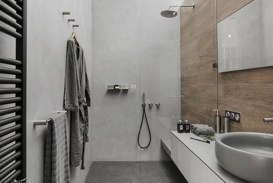 Douche derrière une cloison vitrée dans la salle de bain combinée