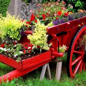 Vieux chariot comme parterre de fleurs