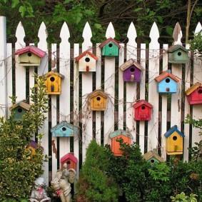 Décoration d'une clôture en bois avec nichoirs faits maison