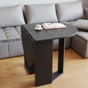Table noire devant un canapé gris